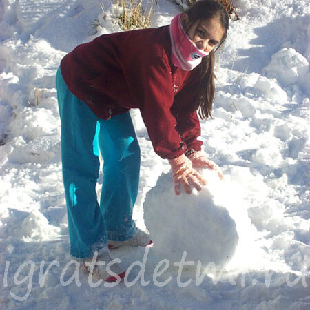 Девочка скатывает снежный ком